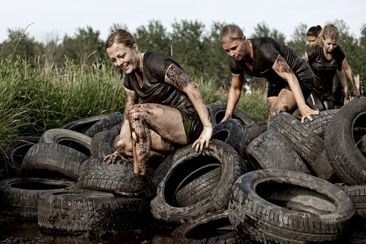 group of friends crossing tyre obstacle during mud run